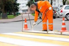 Улица маркировки работника дороги выравнивает скрещивание зебры Стоковые Фото
