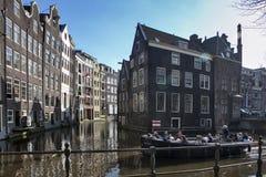 улицы amsterdam Взгляд канала Амстердама, велосипеды на мосте Время вечера Свет захода солнца Стоковая Фотография