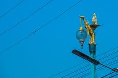 Уличный свет изолированный на голубом небе Золотая скульптура птицы Таиланд Стоковое Изображение