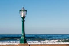 Уличный фонарь на стене с океаном стоковое фото