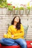 Удобная женщина сидя снаружи с апельсиновым соком Стоковая Фотография RF