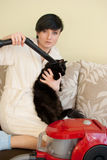 Женщина очищает кота с уборщиком vacum Стоковые Фотографии RF