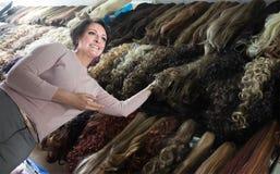 Удовлетворенная женщина выбирая расширение волос в салон Стоковые Фото