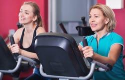 Удовлетворенные пожилые люди и молодые женщины разрабатывая в спортзале Стоковые Фото
