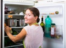 Удовлетворенный холодильник домохозяйки близко заполненный Стоковые Фото
