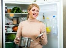 Удовлетворенный холодильник домохозяйки близко заполненный Стоковые Фотографии RF