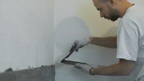 Улучшение дома, реновация - tiler рабочий-строителя кроет черепицей, прилипатель стены керамической плитки, лопатка с минометом сток-видео