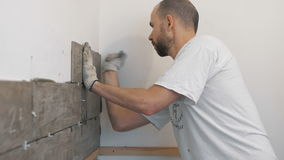 Улучшение дома, реновация - tiler рабочий-строителя кроет черепицей, прилипатель стены керамической плитки, лопатка с минометом акции видеоматериалы