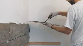 Улучшение дома, реновация - tiler рабочий-строителя кроет черепицей, прилипатель стены керамической плитки, лопатка с минометом видеоматериал