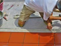 Улучшение дома, реновация - tiler рабочий-строителя кроет черепицей, керамический прилипатель плиточного пола Стоковые Фото