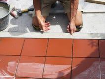 Улучшение дома, реновация - tiler рабочий-строителя кроет черепицей, керамический прилипатель плиточного пола Стоковое Изображение