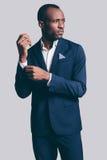 Улучшите стиль Красивый молодой африканский костюм человека полностью регулируя его рукав и смотря отсутствующий пока стоящ проти стоковые изображения