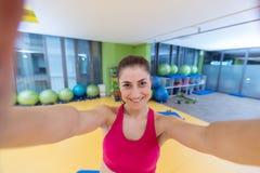 Улыбка женщины спорта на изображении собственной личности камеры на спортзале, изображении себя маленькой девочки работая фитнес- Стоковые Изображения