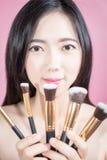 Улыбка и потеха женщины длинных волос азиатские молодые красивые, касаются ее стороне и держатся косметический комплект щетки пор Стоковые Фотографии RF