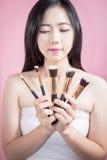 Улыбка и потеха женщины длинных волос азиатские молодые красивые, касаются ее стороне и держатся косметический комплект щетки пор Стоковые Изображения