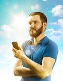 Улыбка молодого человека и держать телефон стоковая фотография rf