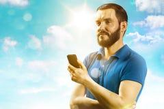 Улыбка молодого человека и держать телефон стоковое фото