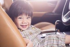 Улыбка ребёнка Азии в роскошном автомобиле потому что пошл вне путешествовать Стоковое Фото