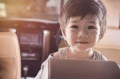Улыбка ребёнка портрета азиатская в роскошном автомобиле с космосом для текста Стоковые Фото