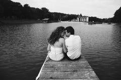 Улыбка человека и женщины сидя на мосте Стоковые Фотографии RF