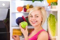 Улыбка яблока женщины зеленая, холодильник Стоковые Фото