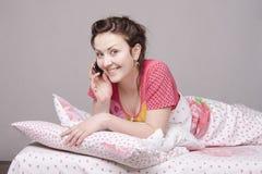 Улыбки девушки говоря на телефоне в кровати Стоковые Изображения RF
