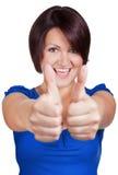 Улыбки женщины и показывают ей большие пальцы руки Стоковое Изображение