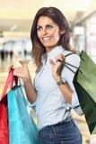 Улыбки женщины покупок на универмаге стоковые изображения