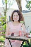 Улыбки молодой женщины на кафе Стоковое Фото