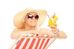 Ультрамодная женщина выпивая коктеиль на lounger солнца Стоковое Фото