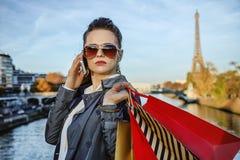 Ультрамодная женщина с хозяйственными сумками в Париже используя smartphone Стоковое фото RF
