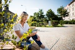 Ультрамодная зрелая женщина наслаждаясь новым телефоном устройства Стоковое Изображение