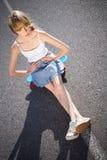 Ультрамодная молодая женщина сидя на ее скейтборде стоковое изображение rf