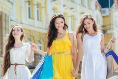 Ультрамодная подруга для прогулки Девушки держа хозяйственные сумки и wa Стоковые Фотографии RF
