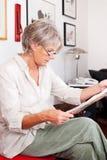Ультрамодная старшая женщина читая газету Стоковые Изображения RF
