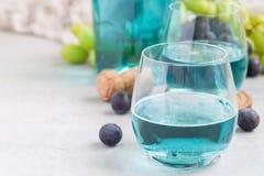 Ультрамодное голубое вино moscato в виноградине стекла, зеленых и красных на предпосылке, горизонтальной Стоковое фото RF