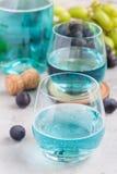Ультрамодное голубое вино moscato в стекле и в виноградине бутылки, зеленых и красных на предпосылке, вертикальной Стоковые Изображения
