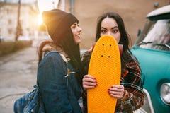 2 ультрамодное и скейтбордисты девушек модной улицы шутя и усмехаясь Стоковая Фотография