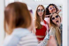 Ультрамодные женские друзья пробуя на стильных солнечных очках смотря в зеркале, усмехающся, имеющ потеху в вспомогательном магаз Стоковое Изображение RF