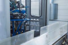 Фабрика воды - намочите линию разлива для обрабатывать и разливать чисто ключевую воду по бутылкам в малые бутылки стоковое изображение rf