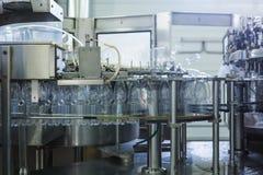 Фабрика воды - намочите линию разлива для обрабатывать и разливать чисто ключевую воду по бутылкам в малые бутылки стоковое изображение