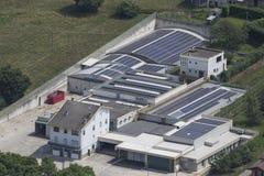 Фабрика вполне панелей солнечных батарей с зеленой arou травы и деревьев стоковое изображение