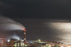Фабрика против моря в лунном свете Стоковое Фото