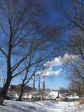Фабрика пускает по трубам с белым дымом около реки в зиме Стоковое Фото