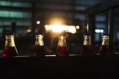 Фабрика соды, полные бутылки, который нужно свернуть в линии со светом захода солнца стоковые фото