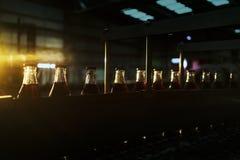 Фабрика соды, полные бутылки, который нужно свернуть в линии со светом захода солнца стоковое фото