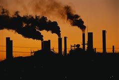 Фабрика с дымовыми трубами на заходе солнца Стоковое Фото
