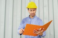 Файлы удерживания инженер-электрика пока носящ шлем безопасности средств индивидуальной защиты Стоковое фото RF