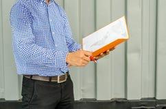 Файлы удерживания инженер-электрика пока носящ шлем безопасности средств индивидуальной защиты на строительной площадке Стоковое Изображение RF