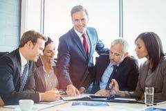 Файл показа бизнесмена к сотрудникам в конференц-зале Стоковая Фотография